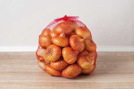 5 kg farm onions in a red pp mesh bag. Polypropylene net sack with 11 lb of organic onions on a brown floor indoors. Buying fresh vegetables in bulk. Front view.