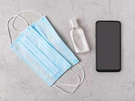 Blue disposable medical face mask, hand sanitizer and smartphone over gray background. Copy space on a device screen. Protection against viral infections, virus and flu. Top view. 免版税图像