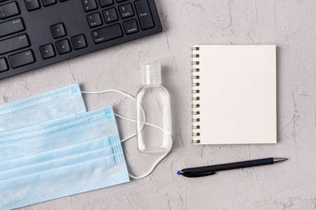 Copy space on spring notebook near medical face mask, hand sanitizer and PC keyboard over textured gray backgroung. Protection against virus , flu and viral infections, concept. Top view. 免版税图像