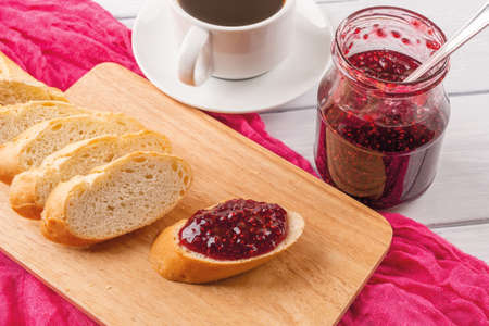 Tasty sandwich with raspberry jam on a wood cutting board, jam jar and cup of tea or coffee on a wood table. Traditional homemade sweet red berry jelly, marmalade or confiture as ingredient for breakfast. Top view. 免版税图像