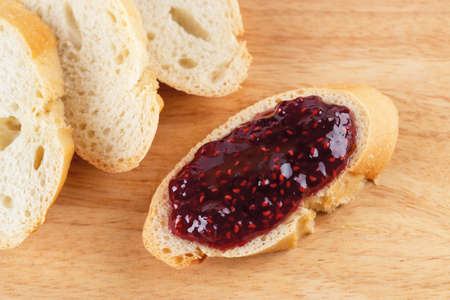 Delicious sandwich with raspberry jam and few baguette slices on a wood cutting board. Traditional homemade red berry jelly, marmalade or confiture as ingredient for sweet pastries and breakfast. Top view.