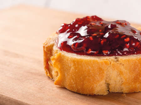 Close-up of delicious sandwich with raspberry jam on a wood cutting board. Traditional homemade red berry jelly, marmalade or confiture as ingredient for sweet breakfast or pastries. Front. view.