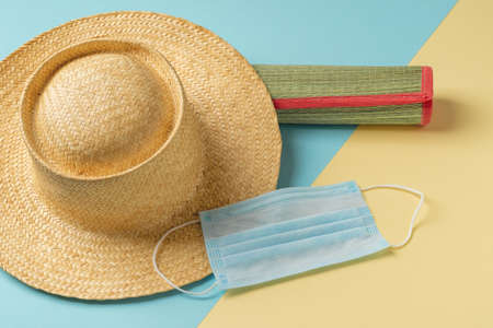 Medical face mask and wide brim straw hat on a rolled up wicker beach mat against yellow blue background. Protection against   flu during summer vacation or travel concepts. Top view. 免版税图像