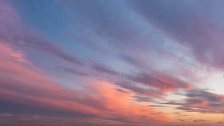 Dramatic vanilla skyscape. Purple orange sunset clouds against blue sky. Scenic dynamic low clouds in a twilight heaven. Weather forecast, meteorology. Beauty in nature.