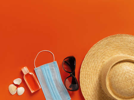 Wide brim straw hat, sunglasses and blue medical face mask on a yellow background. Protection against viral infections,   flu during summer vacation or travel concepts. Top view.