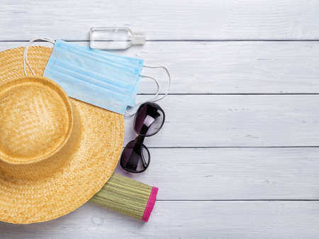Wide brim straw hat on a rolled up beach mat, sunglasses, medical face mask and hand sanitizer on a white wood desk. Protection against  flu during summer vacation or travel. Copy space. Top view.