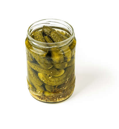 Delicious pickled cornichons in an open glass jar isolated on white background. Whole green gherkins marinated with dill and mustard seeds. Crunchy baby pickles. Tasty canned vegetables. Front view.
