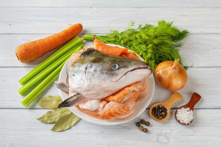 Raw ingredients for cooking fish stock: fresh salmon head and bones, vegetables, salt and pepper over a white wood table. Red fish broth bouillon recipe. Homemade seafood healthy eating. Top view. 免版税图像