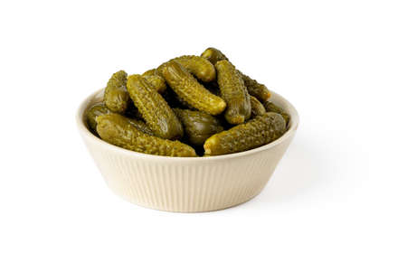 Pickled gherkins in a beige ceramic bowl isolated on a white background. Whole green cornichons marinated with dill, garlic and mustard seeds. Crunchy baby pickles. Tasty canned vegetables. Front view.