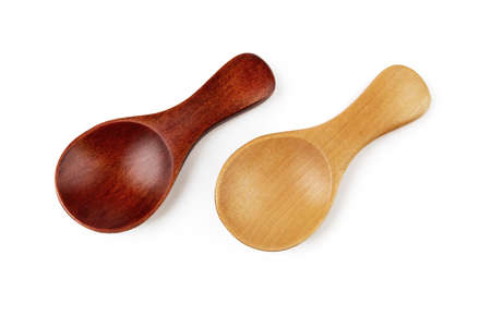 Pair of small wooden spoons for tea or shugar isolated on white background. Dark and light empty spoons for food design. Beautiful eco-friendly tableware made of natural wood. Living green lifestyle. Top view. 免版税图像