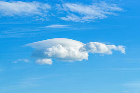 Small lenticular cloud against translucent cirrus clouds high in a clear blue sky. Different cloud types and atmospheric phenomena. Skyscape on a sunny day. Meteorology and weather forecast. 免版税图像