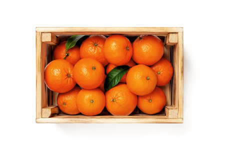Sweet ripe orange tangerines in a wooden crate isolated on white background. Fresh citrus in a wood box. Eco-friendly rustic style containers for fruits and vegetables. Vegetarian and healthy eating. Top view.