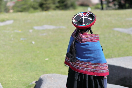 Peruvian woman in traditional costume in Sacsayhuaman at Cusco, Peru