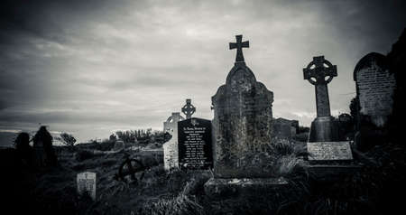 Ireland celtic cross at medieval church cemetery Old spooky cemetery. Haunted cemetery. Scary place. Old graves