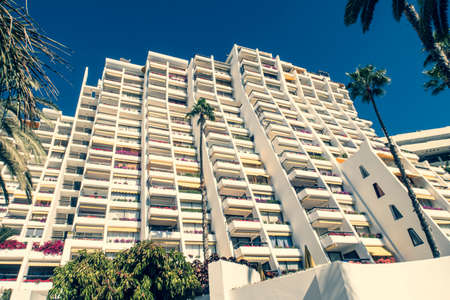 Detail of a facade with palm tree in the foreground.Highly repetitive downtown condominium building facade with balconies. Imagens