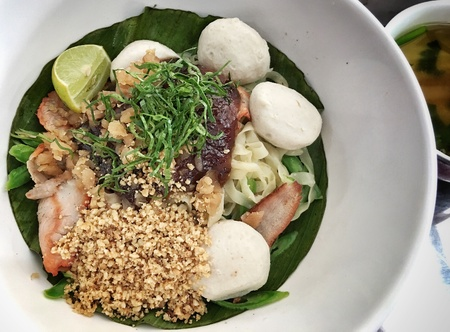 style: A bowl of spicy thai style egg noodle with red pork crunch peanut and pork ball Stock Photo