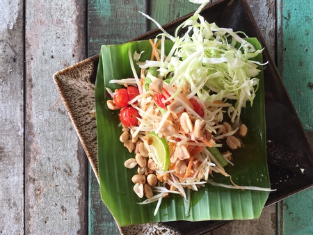style: Thai style Papaya salad with banana leaf on vintage wooden table Stock Photo