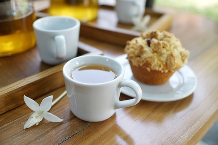 A cup of tea with Muffin on wooden table in the garden
