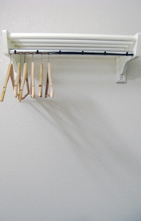 hangers: clothes hangers on wall rack Stock Photo
