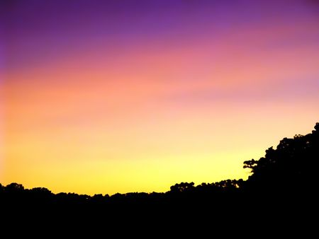 sunset in purple and gold with silhouetted treeline.  Near Joliet, IL, USA Banco de Imagens
