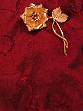 Gold metallic rose on red satin