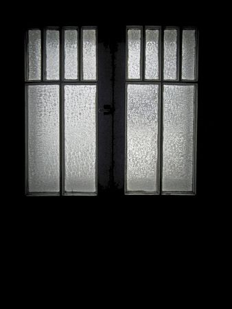 window view: Old casement window with frosted glass panes divided by muntins. Interior silhouette view on black background.  Vintage circa 1900