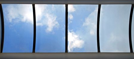 Looking straight up through the arched skylight, blue sky and fluffy white clouds
