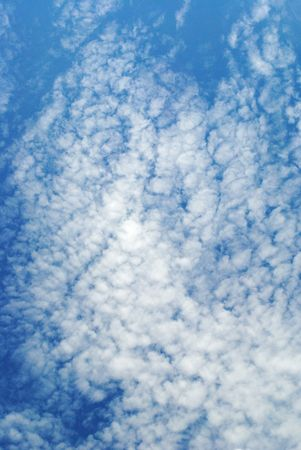 Bright cirrocumulus clouds in a deep blue sky; this