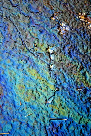 ambivalence: Iridescent oil slick on wet asphalt  Stock Photo