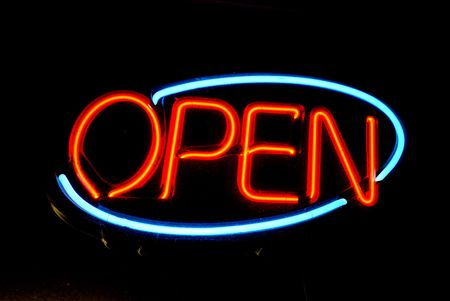 bright oval neon sign proclaims the business is open. Vintage 1950s