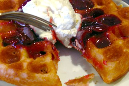 Belgian waffles with cherries and whipped cream.  Delicious!