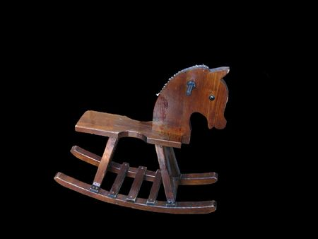 Old wooden rocking horse with its mane worn away to stubble; on black background Stock Photo