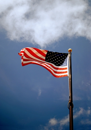 Flag of the United States flies proudly in the deep blue sky. Stock Photo