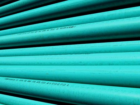 PVC plastic pipe stacked at the construction site ready to be laid as a sewer line; bright highlights and deep shadows make interesting abstract pattern.  Good background for your text.
