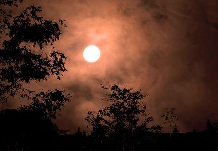 Full moon haunts a cloudy copper-colored autumn sky.