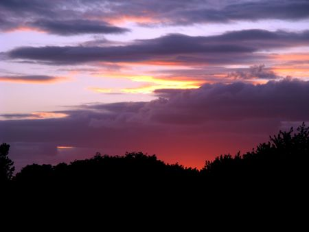 Last rays of sunset impart a rosy glow to the deep purple clouds. Stock Photo