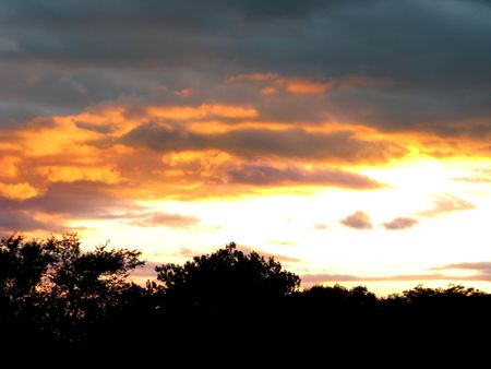 Dark grey storm clouds give way to bright golden sunset.