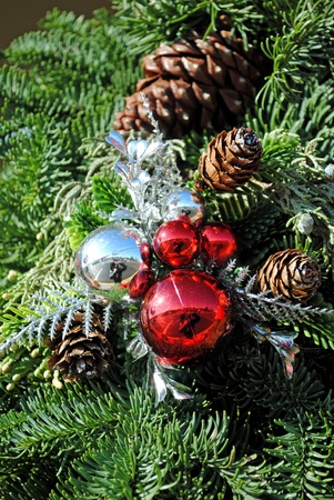 Shining ornaments and pine cones among evergreen branches.