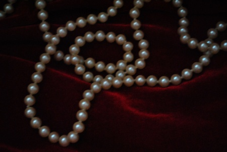 gleams: A string of pearls gleams softly through the mysterious dark.  Copy space for text.