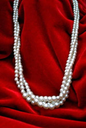 Triple strand of white pearls on a red velvet background. Plenty of copy space.