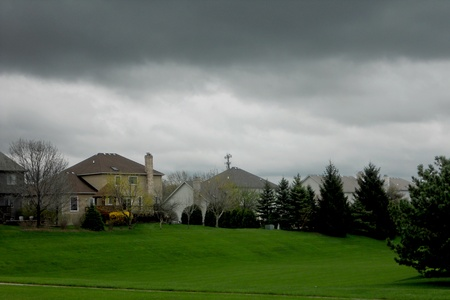 Storm clouds lower over the suburban houses.