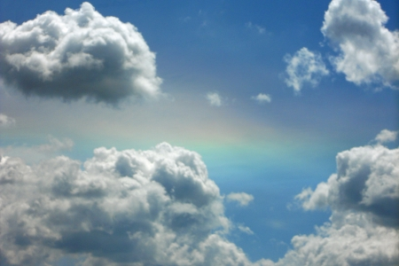 Bright puffy clouds in a blue sky, with just a touch of rainbow shining through. Stock Photo