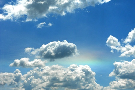 fortunate: Bright puffy clouds in a blue sky, with just a touch of rainbow shining through. Stock Photo