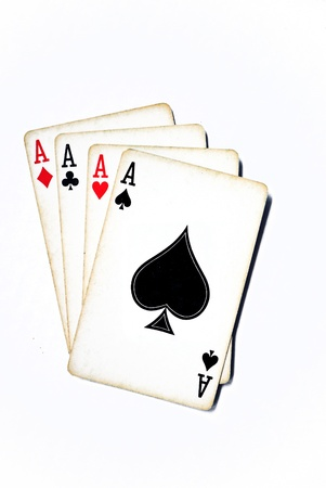 Four aces from a worn deck of playing cards; isolated on white Фото со стока