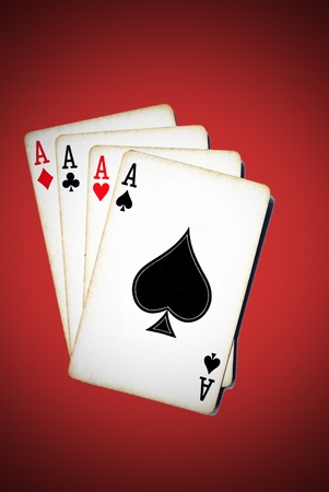 Four aces from a worn deck of playing cards; red background with vignette effect. Stock Photo