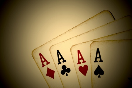 Four aces from an old worn deck of playing cards. Sepia tone and vignette effect.