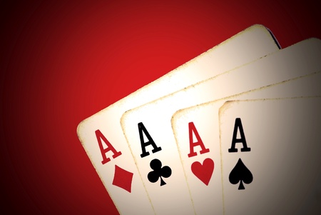 Four aces from an old worn deck of playing cards. Red background and vignette effect.