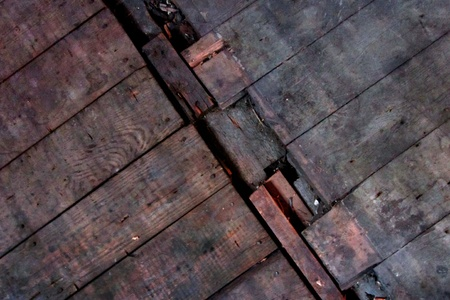 Distressed floorboards at joint of old floor and even older floor.  Good grunge background. photo