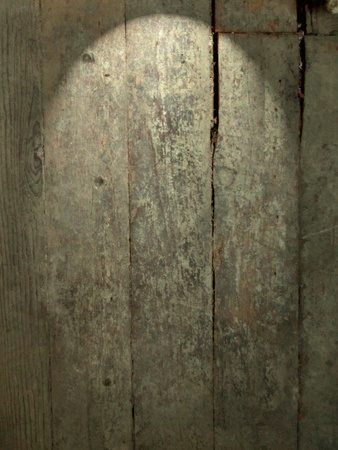 Distressed wooden board surface with down-light effect makes good grunge background.