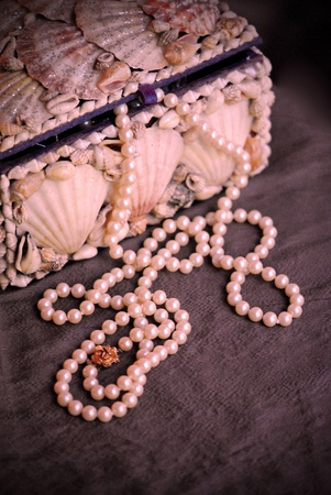 Pearl necklace spilling from a shell-covered jewelry box.